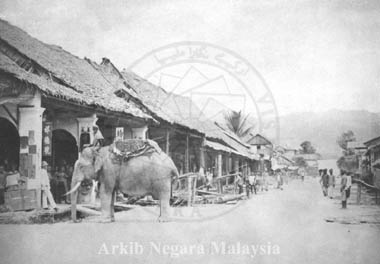"The main mining centre of Larut between 1840-50 was at Kelian Pauh, where the Taiping gaol (jail) now stands. (Kelian Pauh was re-named Taiping meaning ""Peace"" after the Larut War). An elephant which was used by the miners escaped into the nearby Kamunting jungles and when recaptured was found to be covered with mud rich in tin ore. This led to a wild rush to Kamunting - to the ""new mines"", or Kelian Baharu, later re-named Kamunting. This photograph shows Kamunting Village in about 1890. The main mode of transport then was ""by elephant"" which can be seen on the left. Source: Arkib Negara Malaysia"